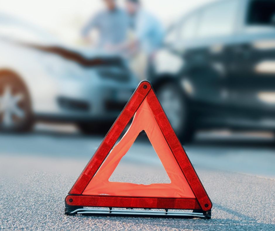 a reflective triangle on the ground in the camera's focus in front of a car accident that is out of focus